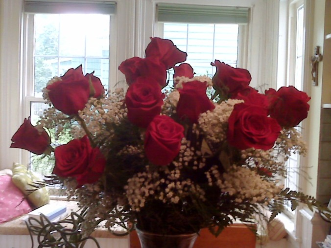 photo of 24 red roses with greenery and baby's breath